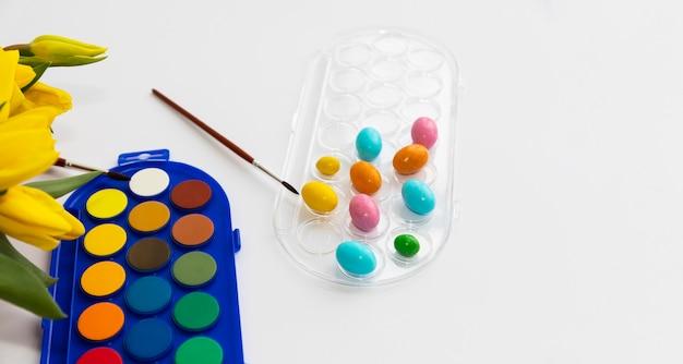 Tintura di uova fai da te per pasqua. colori ad acquerello, pennelli e piccoli testicoli.