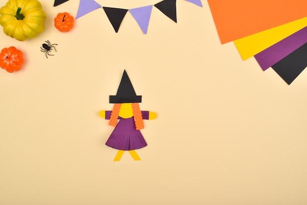 Halloween fai da te. facciamo una strega con la carta colorata. istruzioni passo passo. passaggio 9: incolla il cappello e i capelli sulla testa.