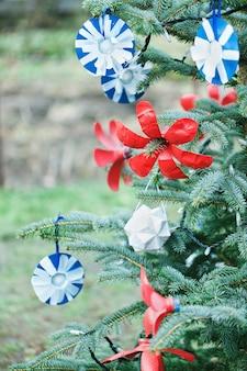 Decorazione fatta a mano fai da te fatta di carta e bottiglia di plastica su un albero di natale
