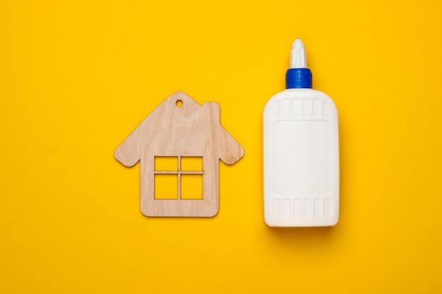 Concetto di casa fai da te. statuetta in legno mini casa e una bottiglia di colla su uno sfondo giallo. vista dall'alto