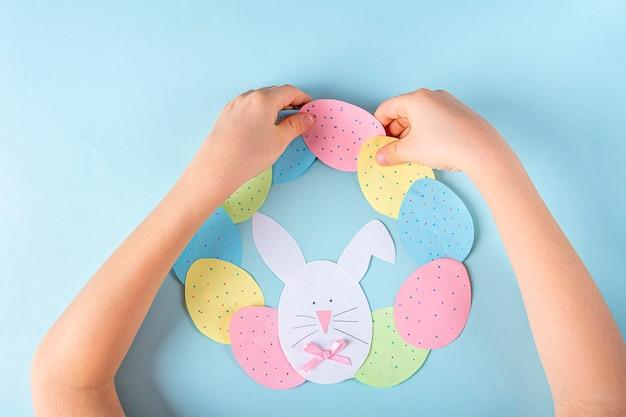 Creatività fai da te e per bambini. istruzioni passo passo: come realizzare una ghirlanda pasquale di carta. incolla le uova di carta e il coniglio per fare un cerchio come una ghirlanda. artigianato pasquale fatto a mano per bambini.