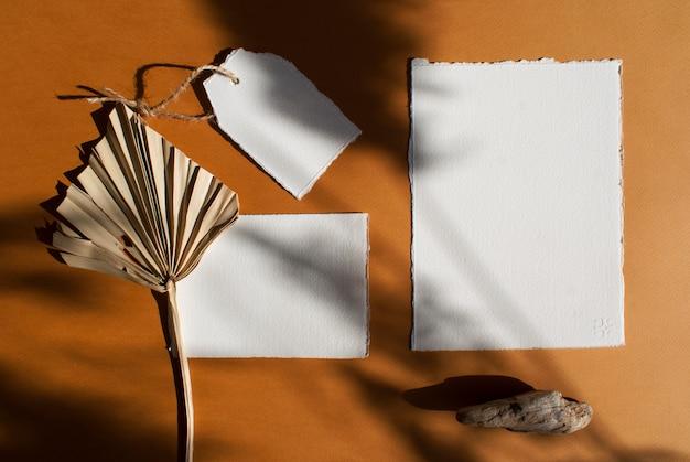 Carta bianca fai-da-te poster bianco invito a nozze kit e tag con foglia di palma essiccata sul tavolo in terracotta martellata. modello moderno ed elegante per l'identità del marchio. vista piana, vista dall'alto
