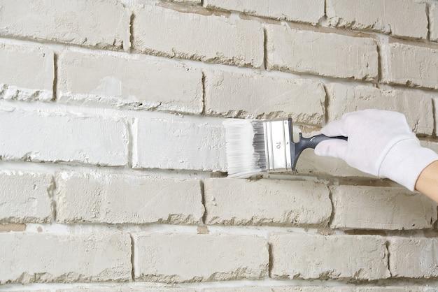 Riparazione di pareti fai da te, donna che dipinge un muro di mattoni bianchi con un pennello