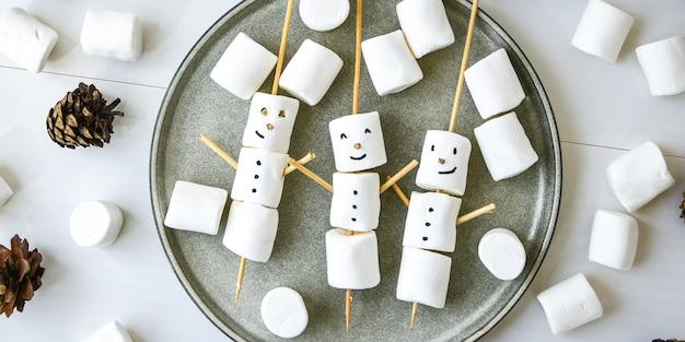 Marshmallow bianco fai da te dolce regalo per bambini divertente pupazzo di neve marshmallow nel piatto. vista dall'alto. passo dopo passo. coni di natale. decorazioni natalizie