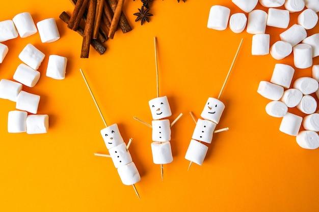 Marshmallows bianchi fai da te dolci per bambini divertenti marshmallow pupazzo di neve. vista dall'alto. passo dopo passo. decorazioni natalizie