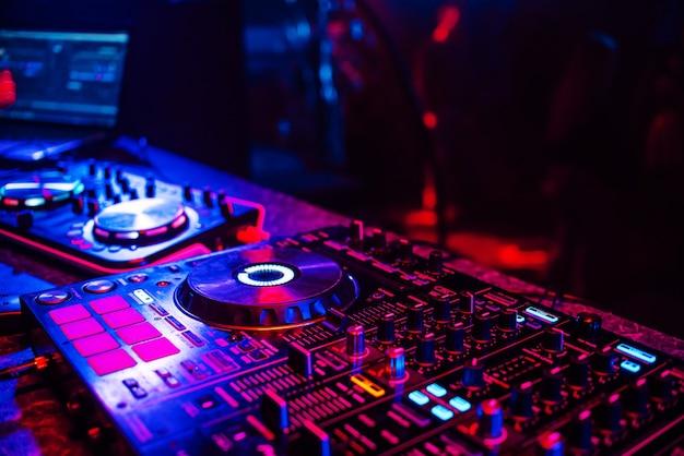 Console dj per mixare musica con persone sfocate che ballano a una festa in discoteca