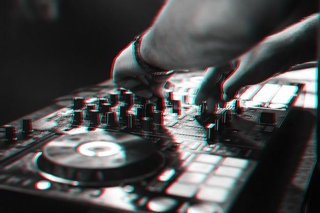 Dj suona musica con le sue mani su un controller mixer durante un concerto di musica elettronica dal vivo