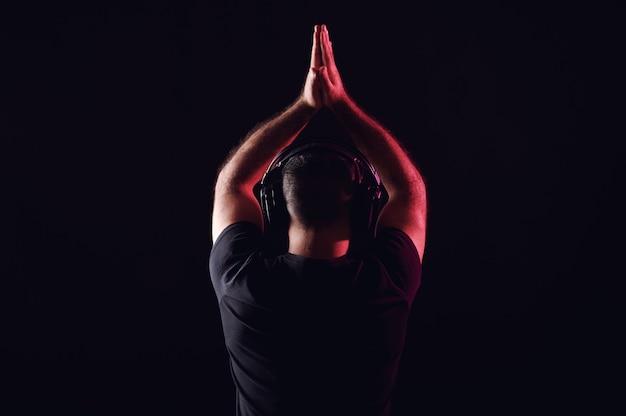 Dj suona un set musicale e batte le mani. l'uomo ascolta la musica con le cuffie e ha alzato le mani.