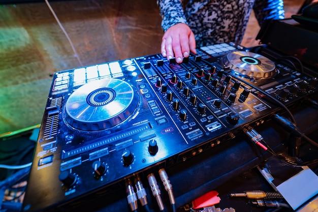 Dj suona musica alla moda su una console mixer in discoteca