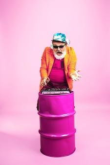 Dj. ritratto di uomo anziano hipster in occhiali alla moda isolato su sfondo rosa studio. tecnologia e concetto di stile di vita anziano gioioso. colori di tendenza, per sempre giovinezza. copyspace per il tuo annuncio.