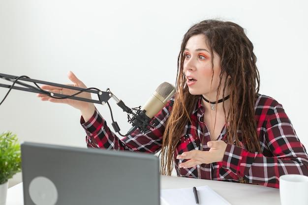 Dj, conduttore radiofonico e concetto di blog - giovane donna che lavora in studio.