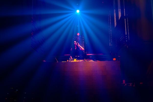Dj sul palco in discoteca night club mescolando musica techno