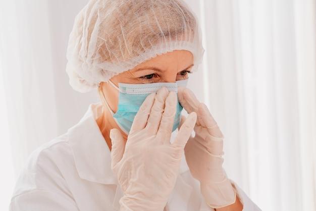 Il dottore aggiusta la mascherina per proteggersi dal virus covid