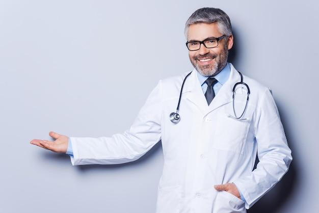 Dottore che pubblicizza il tuo prodotto. medico maturo allegro che guarda la macchina fotografica e indica via mentre si trova in piedi su uno sfondo grigio
