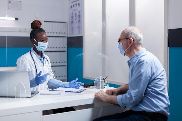 Dottore di etnia afroamericana che indossa la maschera facciale