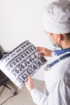 Il medico all'appuntamento ispeziona ed esamina la scansione ct del torace e della cavità addominale. foto di concetto sulla diagnosi di malattie in pneumologia, patologia polmonare, malattie infiammatorie dei bronchi, tubercolosi