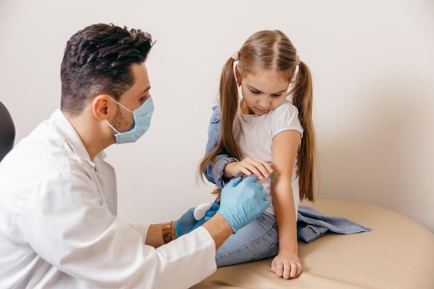 Un medico di nazionalità araba o turca ha somministrato alla bambina una vaccinazione contro il coronavirus. le ragazze sono ferite. foto di alta qualità