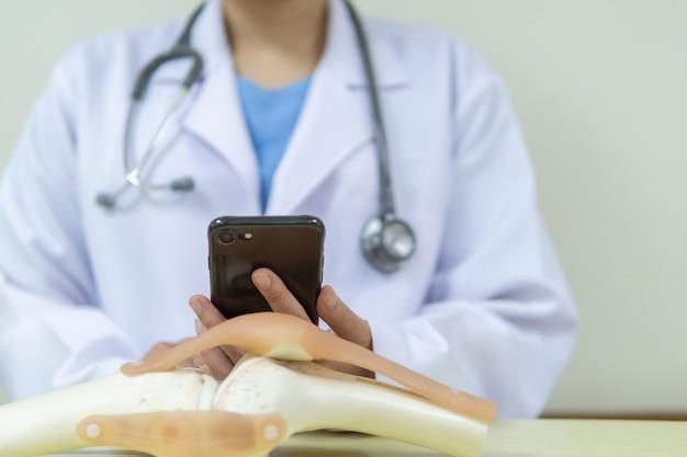 Il dottore sta guardando gli appuntamenti per i pazienti che richiedono un intervento chirurgico di sostituzione del ginocchio