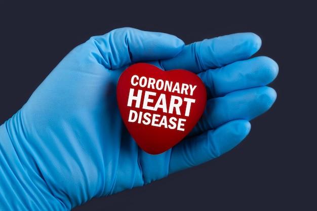 Il dottore in guanti blu tiene un cuore con la malattia coronarica del testo
