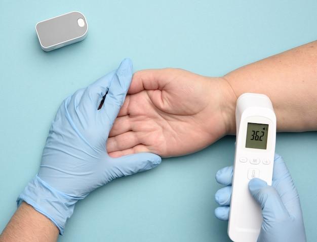 Il dottore in guanti di lattice blu misura la temperatura con un gadget elettronico senza contatto sulla mano di una donna, sfondo blu