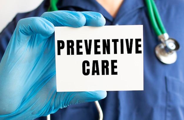 Un medico con una tuta medica blu tiene in mano una carta con il testo cura preventiva.