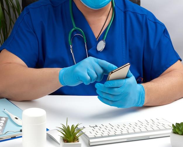 Medico in uniforme medica blu si siede ad una scrivania e utilizza uno smartphone