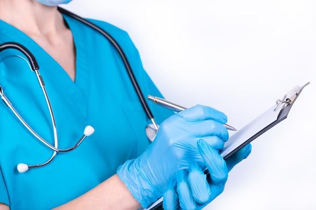 Un medico in uniforme blu e guanti sta prendendo appunti.