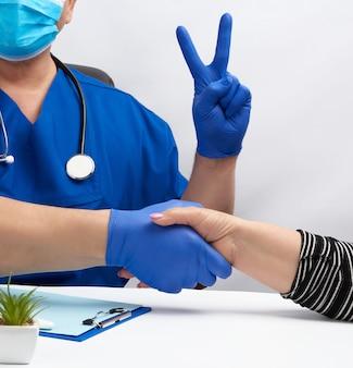 Dottore in uniforme blu si siede ad una scrivania in una poltrona e stringe la mano a una paziente