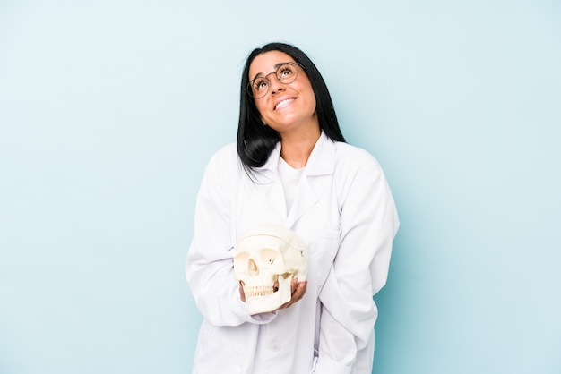 Medico donna caucasica isolata sul blu che sogna di raggiungere obiettivi e scopi