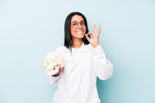 Medico donna caucasica isolata sulla parete blu allegro e fiducioso che mostra gesto giusto.