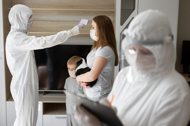Medico controlla la temperatura corporea del paziente usando la pistola a infrarossi per termometro frontale a casa. coronavirus, covid-19, quarantena, alta temperatura.