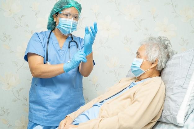 Medico che controlla paziente asiatica donna anziana per proteggere il coronavirus covid-19.