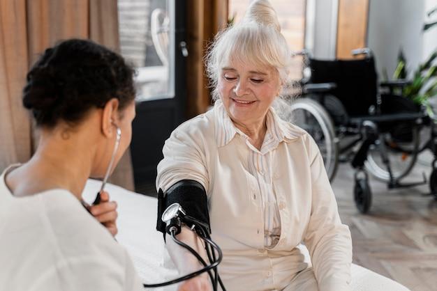 Medico che controlla la pressione sanguigna del suo paziente Foto Premium
