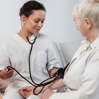 Medico che controlla la pressione sanguigna del suo paziente