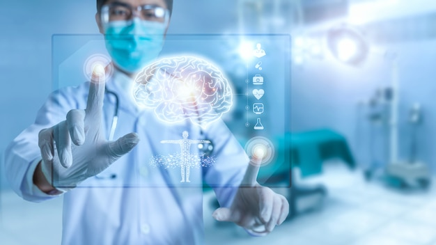 Medico che controlla il risultato dei test del cervello con l'interfaccia del computer, la tecnologia innovativa nel concetto di scienza e medicina, esamina una piastra olografica digitale tecnologica rappresentata