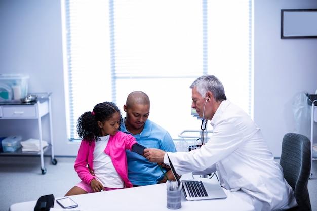 Medico che controlla la pressione sanguigna del paziente