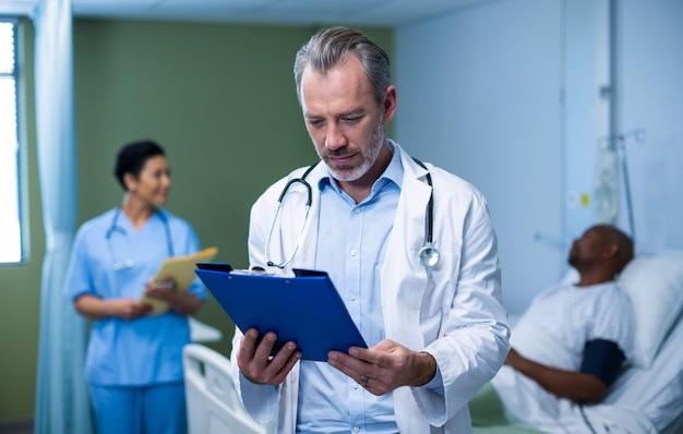 Medico che controlla la relazione paziente in reparto