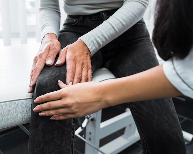 Medico che controlla il ginocchio di un paziente