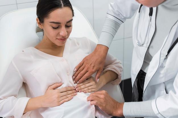 Medico che controlla la pancia di un paziente