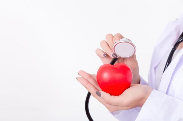 Medico che controlla il cuore rosso con la linea di ecg e stetoscopio. concetto per la salute
