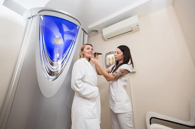 Il medico controlla il livello di abbronzatura sulla pelle della ragazza.