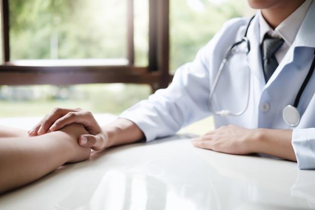 Medico paziente confortante nella stanza di consultazione.