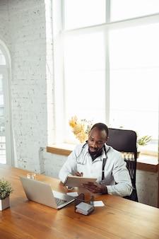 Consulenza medica per paziente online con laptop. medico afroamericano durante il suo lavoro con i pazienti, spiegando le ricette per la droga. duro lavoro quotidiano per la salute e il salvataggio di vite durante l'epidemia.