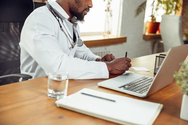 Consulenza medica per il paziente, lavorando con il computer portatile. medico afroamericano durante il suo lavoro con i pazienti, spiegando le ricette per la droga. duro lavoro quotidiano per la salute e il salvataggio di vite durante l'epidemia. Foto Premium