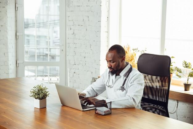 Consulenza medica per il paziente, lavorando con il computer portatile. medico afroamericano durante il suo lavoro con i pazienti, spiegando le ricette per la droga. duro lavoro quotidiano per la salute e il salvataggio di vite durante l'epidemia.