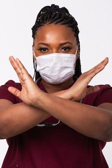 Il medico coronavirus ha incrociato le mani sulla mascherina medica del torace sul muro bianco. no o interrompi il gesto