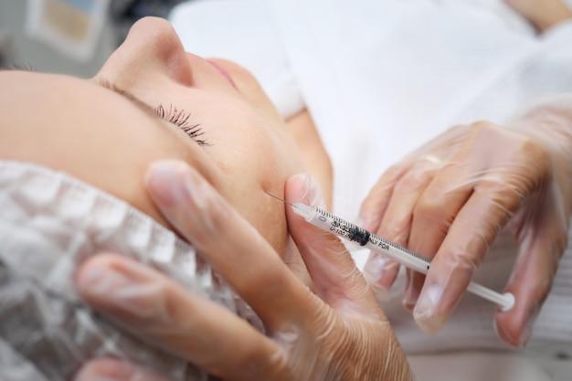 Il medico-estetista aggiunge volume mancante agli zigomi iniettando medicinali simili a gel sotto il fuoco selettivo della pelle