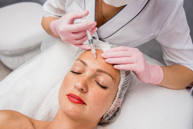 Il medico cosmetologo esegue la procedura di iniezioni facciali. giovane donna in un salone di bellezza.