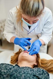 Il cosmetologo medico fa la procedura di aumento delle labbra di una bella donna in un salone di bellezza