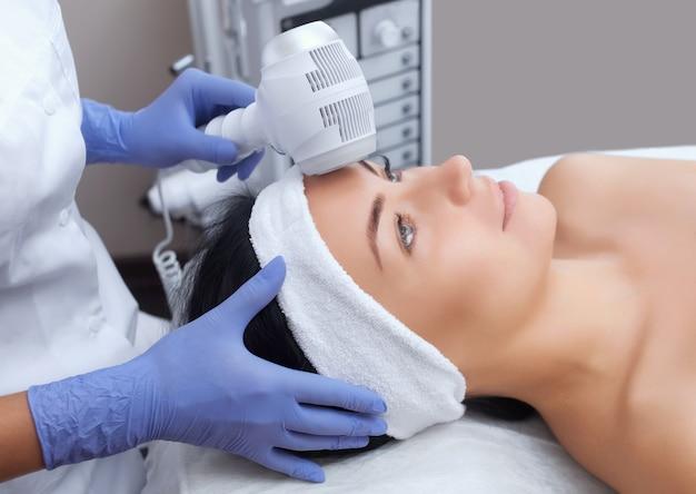 Il medico-cosmetologo rende la procedura crioterapia della pelle del viso di una bellezza